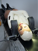 Latex clinic slave patient strapped down on the medical table, and gagged